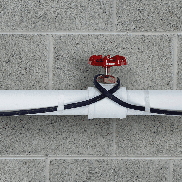 Pipe freeze protection heating cable installed on plastic pipe close