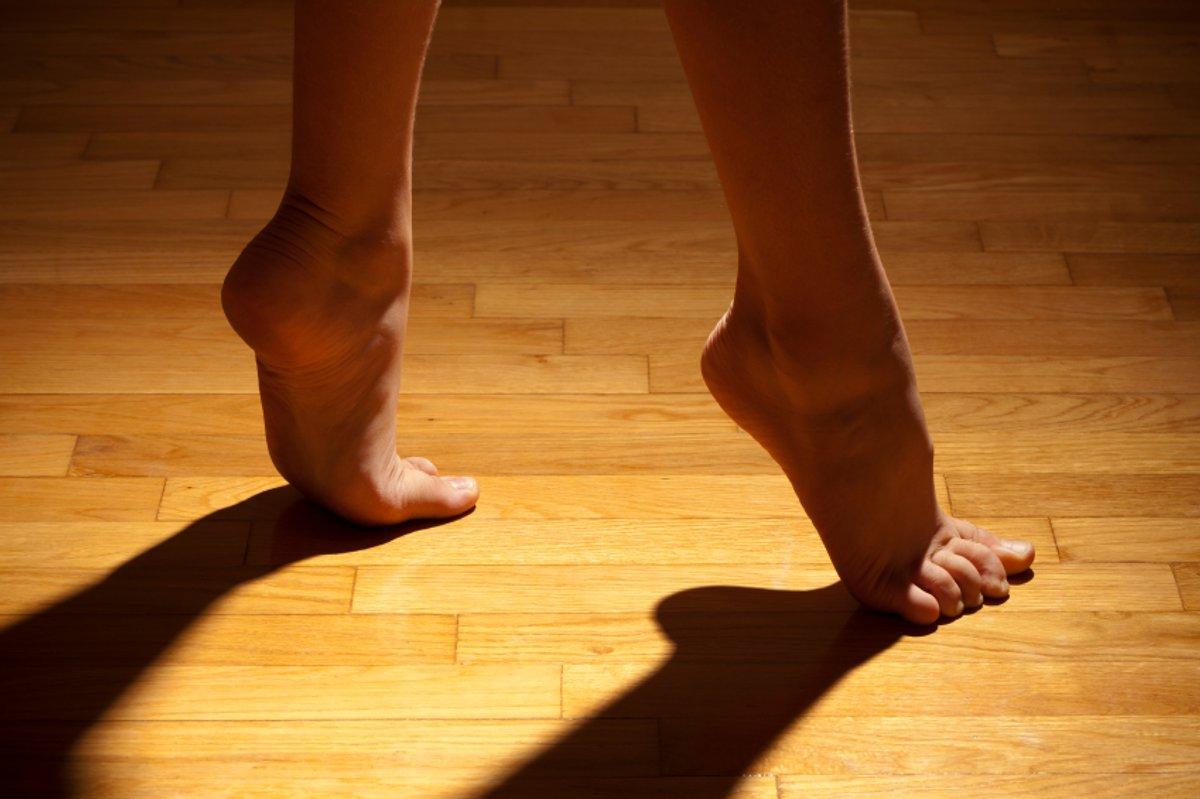 Female Bare Feet Hardwood Floor Shadow Stock Photo