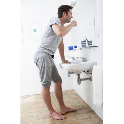 Man brushing teeth at bathroom sink